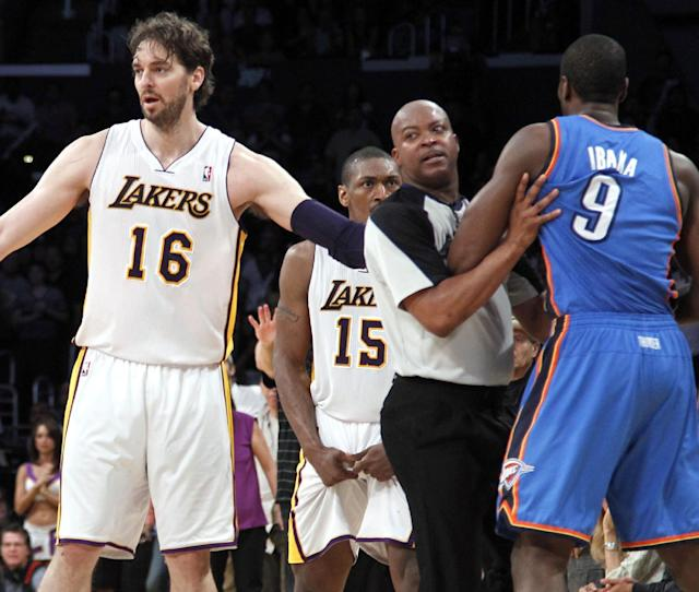 Los Angeles Lakers' Pau Gasol (16), of Spain, stands between an official and Oklahoma City Thunder player after Lakers' Metta World Peace (15) was called for a double flagrant foul and ejected from the game in the first half of an NBA basketball game, Sunday, April 22, 2012, in Los Angeles. (AP Photo/Reed Saxon)
