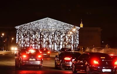 The images of more than 500 people are projected on the facade of the French National Assembly building during the 2015 UN Climate Change Conference (COP21) in Paris The Standing March is the collaborative work by the French artist known as JR and US filmmaker Darren Aronofsky. (Eric Feferberg/AFP)