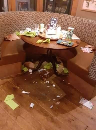 A messy dinner table left in a Harvester restaurant in Colchester, showing napkins and rubbish left on the floor.