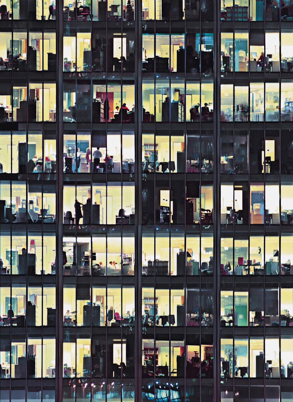An office building buzzing with activity after dark.