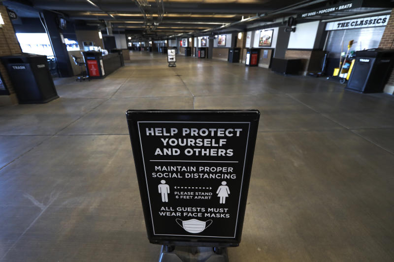 A COVID-19 prevention sign stands in an empty concourse at Guaranteed Rate Field before the Chicago White Sox's home opener baseball game against the Minnesota Twins, Friday, July 24, 2020, in Chicago. (AP Photo/Charles Rex Arbogast)