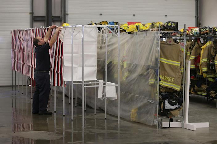 <p>Newmarket Fire and Rescue firefighter Gary Lemoine sets up a voting booth in preparation for tomorrow's primary voters, in Newmarket, N.H. The New Hampshire primary, also known as the first-in-the-nation primary, will be held Feb. 9, with some polling stations opening as early as 6 a.m. and closing around 7 p.m. <i>(Photo: Joe Raedle/Getty Images)</i></p>