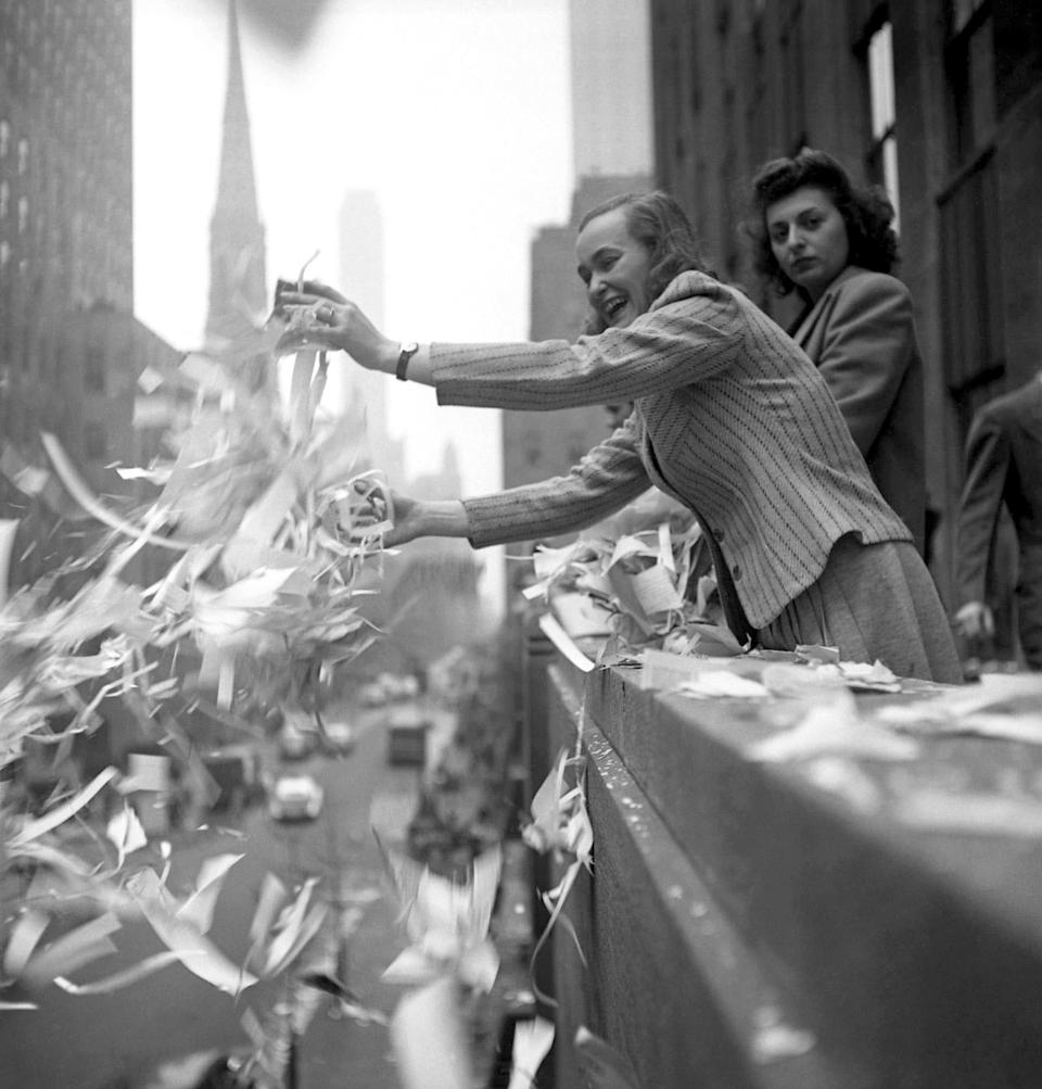 On V-E Day (May 8, 1945), or Victory in Europe Day, a woman laughs as she throws ticker tape over a balcony. The day marks the Allies' formal acceptance of Nazi Germany's unconditional surrender, signaling the end of World War II in Europe.