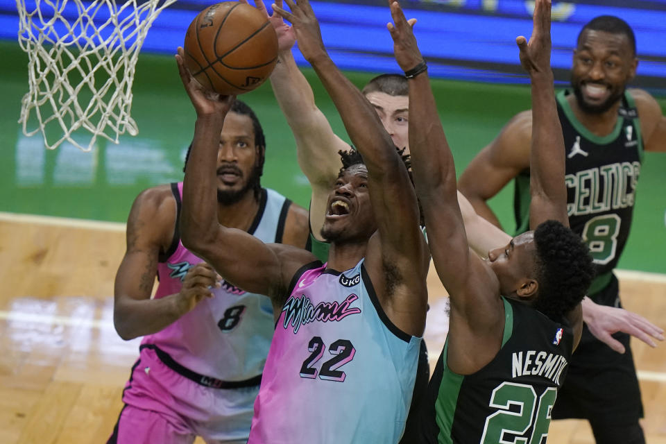 Miami Heat's Jimmy Butler (22) drives toward the basket past Boston Celtics' Aaron Nesmith, right, as Heat's Trevor Ariza (8) looks on in the second half of a basketball game, Sunday, May 9, 2021, in Boston. (AP Photo/Steven Senne)