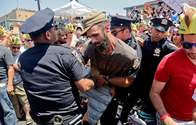<p>Police remove an animal rights activist as they try to protest at the Nathan's Annual Famous International Hot Dog Eating Contest won by Joey Chestnut, Tuesday July 4, 2017, in New York. (AP Photo/Bebeto Matthews) </p>
