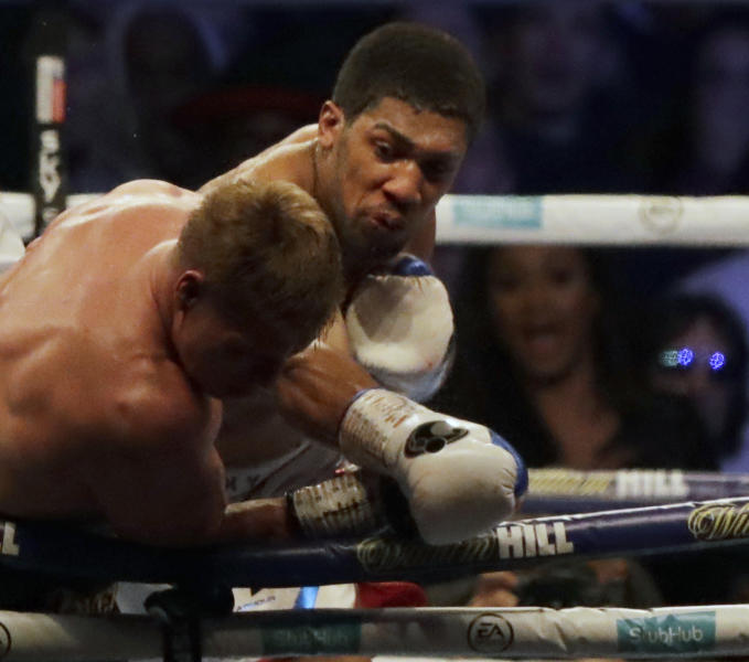 British boxer Anthony Joshua, rear, fights Russian boxer Alexander Povetkin in their WBA, IBF, WBO and IBO heavyweight titles fight at Wembley Stadium in London, Saturday, Sept. 22, 2018. (AP Photo/Matt Dunham)