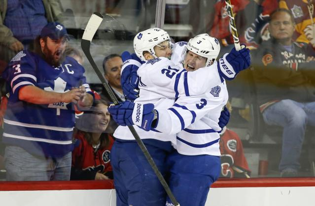Toronto Maple Leafs' James Van Riemsdyk, left, celebrates his goal with teammate Dion Phaneuf against the Calgary Flames during the first period of an NHL hockey game in Calgary, Alberta, Wednesday, Oct. 30, 2013. (AP Photo/The Canadian Press, Jeff McIntosh)