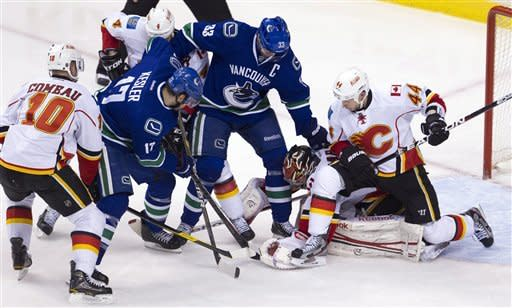 Vancouver Canucks center Ryan Kesler (17) and Vancouver Canucks center Henrik Sedin (33) try to get a shot past Calgary Flames goalie Henrik Karlsson (35) as Calgary Flames defenseman Chris Butler (44), Calgary Flames right wing Blake Comeau (10) and Calgary Flames defenseman Jay Bouwmeester (4) look on during second period NHL hockey action at Rogers Arena in Vancouver, British Columbia, Saturday, March, 31, 2012. (AP Photo/The Canadian Press, Jonathan Hayward)