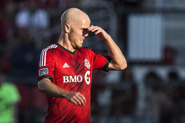 Toronto FC 's Michael Bradley shields his eyes from the sun during first-half MLS soccer game action against D.C. United in Toronto, Saturday, July 5, 2014. (AP Photo/The Canadian Press, Chris Young)