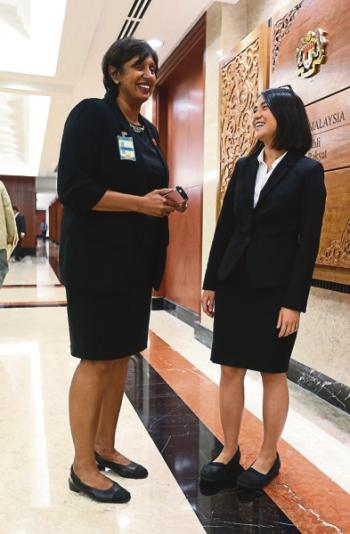 Meera (left) and Tan had to fight their way into Parliament yesterday after security personnel deemed their skirts were too short. — Picture by Razak Ghazali.