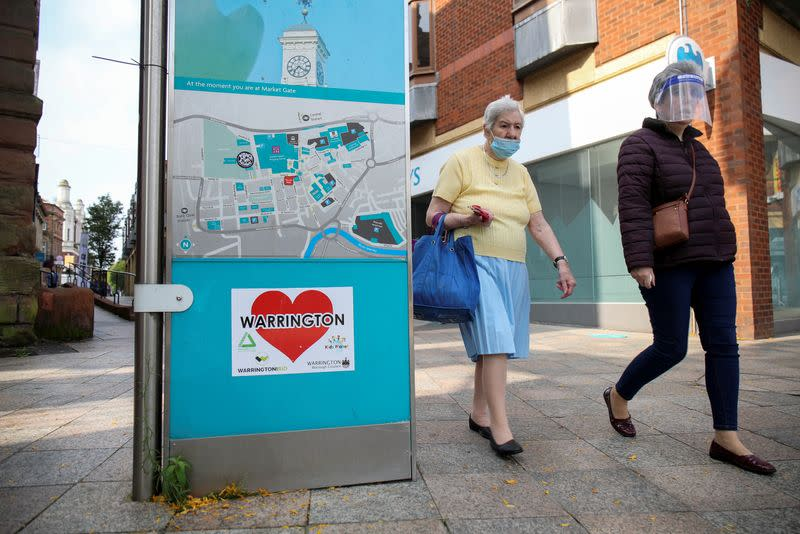 Women wearing a protective mask and a face shield walk past a city map, in Warrington