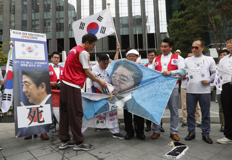 """A South Korean protester uses scissors to cut an image of Japanese Prime Minister Shinzo Abe during a rally denouncing the Japanese government's decision on their exports to South Korea in front of the Japanese Embassy in Seoul, South Korea, Tuesday, July 23, 2019. The signs read """"Punish economic aggression."""" (AP Photo/Ahn Young-joon)"""