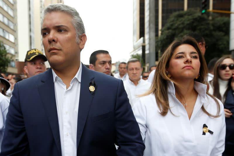 Colombia's President Ivan Duque walks next to with his wife, Maria Juliana Ruiz during a rally against violence, following a car bomb explosion, in Bogota