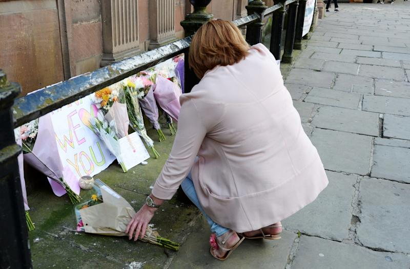 A woman leaves flowers outside St Ann's Church in Manchester - Credit: Ben Birchall/PA