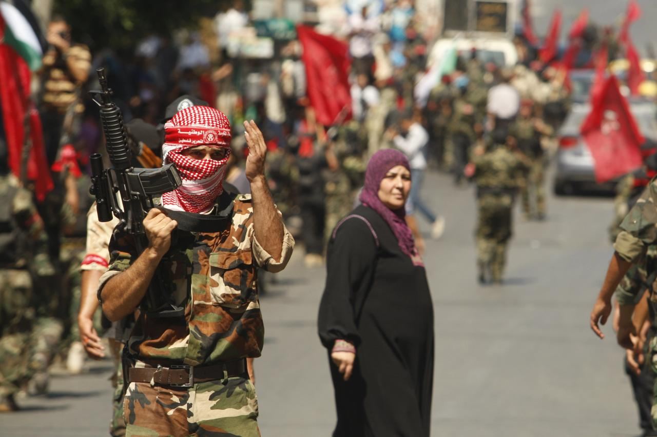 A Palestinian militant from the Democratic Front for the Liberation of Palestine (DFLP) gestures during a military show in Gaza City September 11, 2014. An open-ended ceasefire between Israel and Hamas-led Gaza militants, mediated by Egypt, took effect on August 26 after a seven-week conflict. It called for an indefinite halt to hostilities, the immediate opening of Gaza's blockaded crossings with Israel and Egypt, and a widening of the territory's fishing zone in the Mediterranean. 