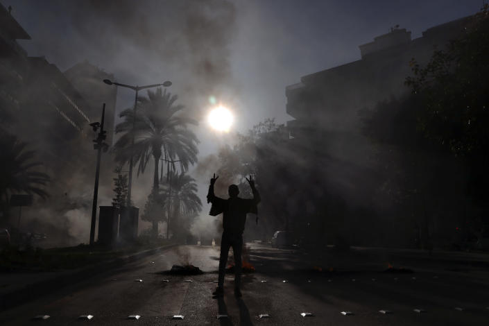 FILE - In this Feb. 24, 2021 file photo, a protester flashes the victory sign, as others burn tires to block a road in front of the house of judge Fadi Akiki during a demonstration calling for the release of anti-government activists detained following riots in northern Lebanon late last month, in Beirut, Lebanon. A public feud in recent weeks among prosecutors has starkly demonstrated how Lebanon's system of sectarian factions is paralyzing Lebanon's judicial system and snarling attempts to root out corruption. (AP Photo/Bilal Hussein, File)