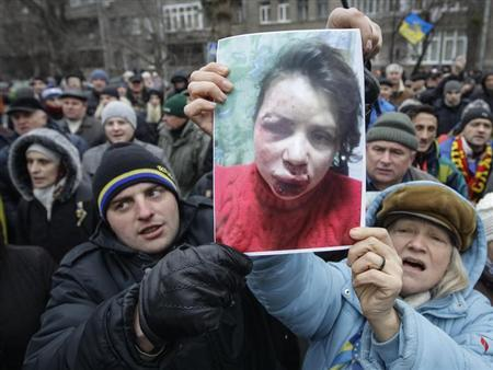 Protesters hold picture of journalist Chornovil, who was beaten just hours after publishing an article on the assets of top government officials, during a protest rally in front of the Ukrainian Ministry of Internal Affairs in Kiev