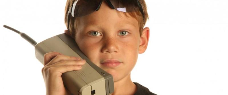 a young boy talks on a old 1980s era Brick Cell phone isolated on white