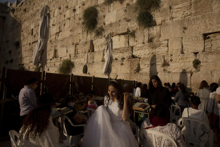 A bride leaves after praying and posing for wedding photos at the Western Wall, the holiest site where Jews can pray, in the shadow of the Mughrabi Bridge, a wooden pedestrian bridge connecting the wall to the Al Aqsa Mosque compound, in Jerusalem's Old City, Tuesday, July 20, 2021. The rickety bridge allowing access to Jerusalem's most sensitive holy site is at risk of collapse, according to experts. But the flashpoint shrine's delicate position at ground-zero of the Israeli-Palestinian conflict has prevented its repair for more than a decade. (AP Photo/Maya Alleruzzo)