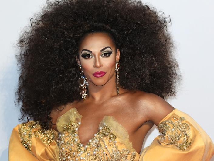 Shangela in gold gown and large brown wig