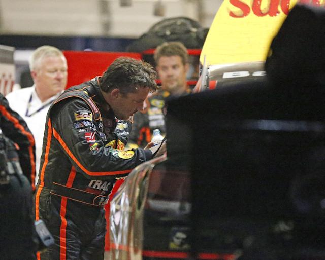 Sprint Cup Series driver Tony Stewart (14) looks over the damage to his car after he hit the wall during a NASCAR Sprint Cup auto race at Atlanta Motor Speedway Sunday, Aug. 31, 2014, in Hampton, Ga.. (AP Photo/Brynn Anderson)
