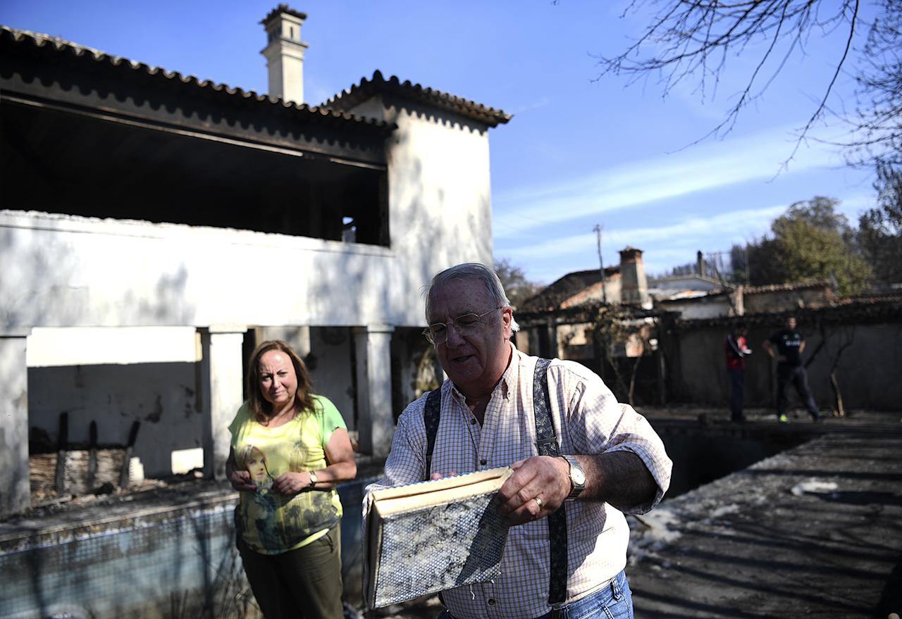 <p>Manuel Rua (R) shows a some of the belongings that he and his wife salvaged from a fire at their house in Lufreu near Penacova on Oct. 17, 2017. (Photo: Francisco Leong/AFP/Getty Images) </p>
