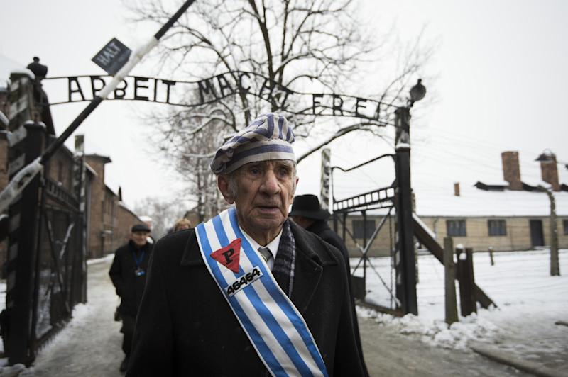 """Survivors walk under the sign saying """"Work makes you free"""" after paying tribute to fallen comrades at the former Auschwitz concentration camp in Oswiecim, Poland, on January 27, 2015 (AFP Photo/Odd Andersen)"""