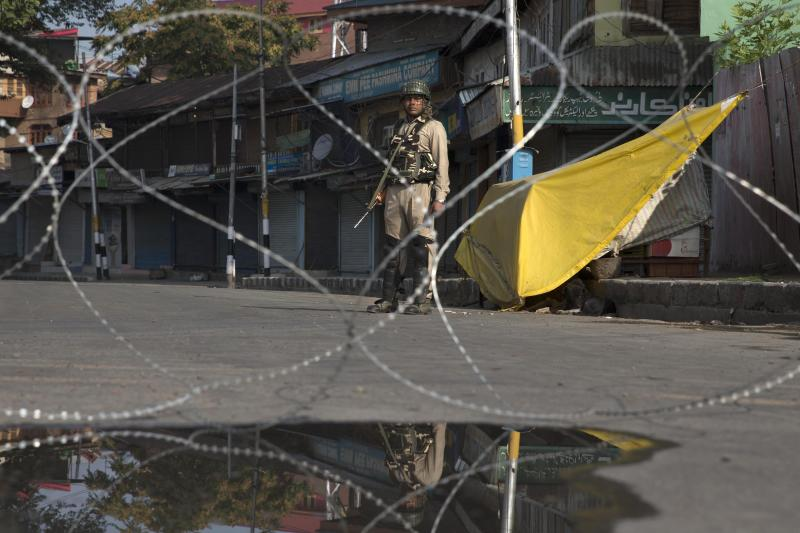 An Indian paramilitary soldier stands guard near a temporary checkpoint during lockdown in Srinagar, Indian controlled Kashmir, Friday, Aug. 23, 2019. The latest crackdown began just before Prime Minister Narendra Modi's Hindu nationalist-led government stripped Jammu and Kashmir of its semi-autonomy and its statehood, creating two federal territories. (AP Photo/Dar Yasin)
