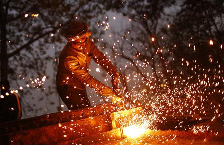 A worker uses a welding torch to weld an iron machine at the construction site of a flyover in New Delhi