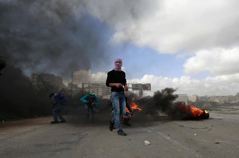 Palestinians burn tires during clashes with Israeli troops, outside Ofer, an Israeli military prison near the West Bank city of Ramallah, Friday, Feb. 15, 2013. Palestinian demonstrators clashed with Israeli soldiers on Friday at a rally held in support of a prisoner observing an intermittent hunger strike to protest his incarceration. The Israeli military said about 200 Palestinians threw rocks at soldiers who responded with tear gas during the rally outside Ofer prison in the West Bank. The protesters called for the release of Samer Issawi, who has been on an on-again, off-again hunger strike for several months as he serves time for alleged terror activity. (AP Photo/Majdi Mohammed)