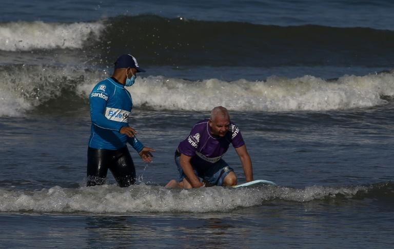 Brazilian surfer Hamilton Fernandes, 63, who suffered a stroke four years ago, rides a wave during at Gonzaga Beach, in Santos, Sao Paulo, Brazil