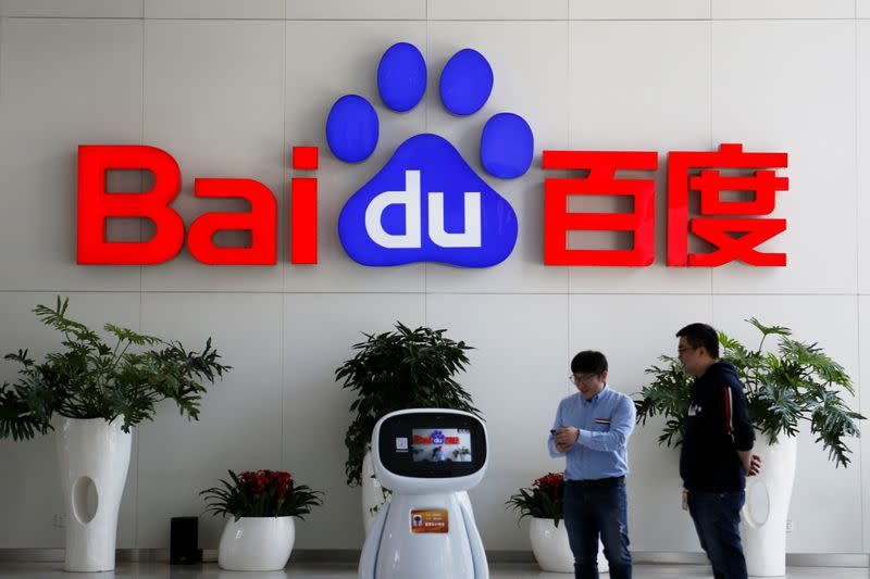 Men interact with a Baidu AI robot near the company logo at its headquarters in Beijing