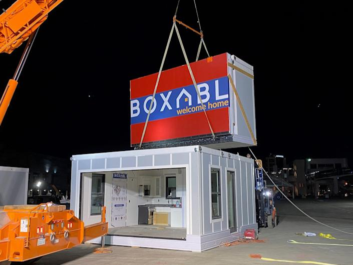 Casita being set up outside with a Boxabl unit being lowered down with a crane.