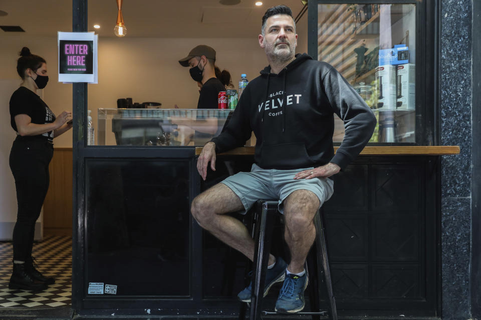Director and founder of Black Velvet coffee shop Darren Silverman poses for a photo outside his cafe in Melbourne, Australia, Wednesday, Oct. 28, 2020. Silverman reopened his coffee shop Wednesday first time since it was closed in late March due to the virus outbreak. (AP Photo/Asanka Brendon Ratnayake)