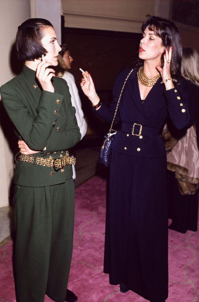 """<p>Princess Caroline and French actress Carole Bouquet enjoyed a smoke break at Chanel's Haute Couture Show, January 1989. Thirty years later, the two would become in-laws when Caroline's daughter <a href=""""https://www.townandcountrymag.com/the-scene/weddings/a27099834/charlotte-casiraghi-dimitri-rassam-grace-kelly-granddaughter-wedding-details/"""" rel=""""nofollow noopener"""" target=""""_blank"""" data-ylk=""""slk:Charlotte Casiraghi married"""" class=""""link rapid-noclick-resp"""">Charlotte Casiraghi married</a> Bouquet's son Dimitri Rassam.</p>"""