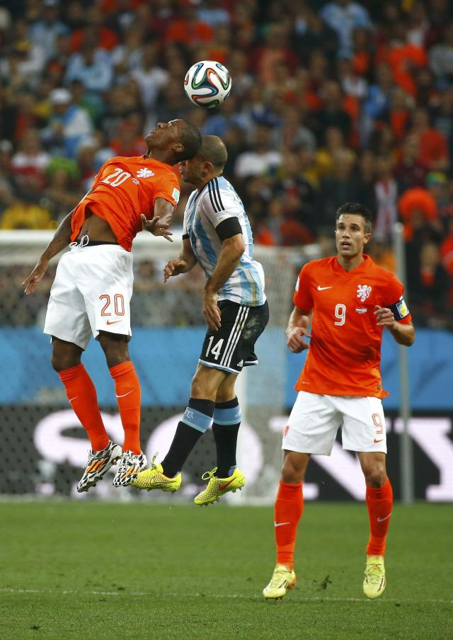 Georginio Wijnaldum (L) of the Netherlands and Argentina's Javier Mascherano collide as they jump for the ball during their 2014 World Cup semi-finals at the Corinthians arena in Sao Paulo July 9, 2014. REUTERS/Michael Dalder (BRAZIL - Tags: SOCCER SPORT WORLD CUP)