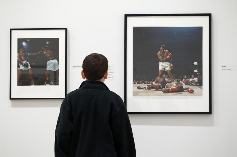 In this photo taken April 22, 2011, Andrew Berg, 12, of Souderton, Pa., views photographs of Muhammad Ali by Neil Leifer, right, and an anonymous photographer, left, at the James A. Michener Museum in Doylestown, Pa. Two American superstars have crossed paths in suburban Philadelphia at the museum, where a pair of photography exhibits called American Icons offers a peek into the lives of Elvis Presley and Muhammad Ali.  (AP Photo/Matt Rourke)