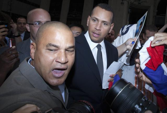 New York Yankees baseball player Alex Rodriguez is surrounded by supporters after leaving Major League Baseball's headquarters in New York