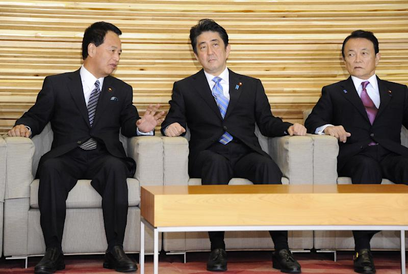 Japan's Prime Minister Shinzo Abe (C) listens to Economic Revitalization Minister Akira Amari (L) and Finance Minister Taro Aso at a cabinet meeting at the prime minister's official residence in Tokyo on November 18, 2014 (AFP Photo/)