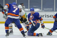 New York Islanders defenseman Scott Mayfield (24) slips in front of Pittsburgh Penguins center Zach Aston-Reese (12) and Islanders right wing Jordan Eberle (7) during the second period of an NHL hockey game, Sunday, Feb. 28, 2021, in Uniondale, N.Y. (AP Photo/Kathy Willens)