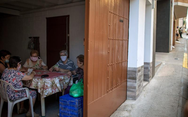 Women play cards inside a house as migrants seeking seasonal work harvesting fruit stand on the street in Fraga