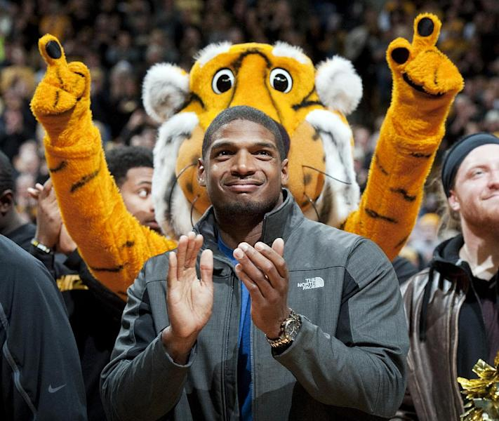 FILE - In this Feb. 15, 2014, file photo, Missouri's All-American defensive end Michael Sam claps during the Cotton Bowl trophy presentation at halftime of an NCAA college basketball game between Missouri and Tennessee in Columbia, Mo. Sam was selected in the seventh round, 249th overall, by the St. Louis Rams in the NFL draft Saturday, May 10, 2014. The Southeastern Conference defensive player of the year last season for Missouri came out as gay in media interviews this year. (AP Photo/L.G. Patterson, File)