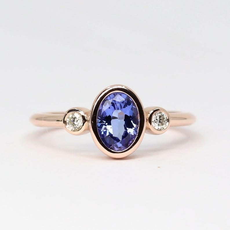 """<p>This striking <a href=""""https://www.popsugar.com/buy/Real-Diamond-Natural-Tanzanite-Engagement-Ring-532654?p_name=Real%20Diamond%20and%20Natural%20Tanzanite%20Engagement%20Ring&retailer=etsy.com&pid=532654&price=404&evar1=fab%3Aus&evar9=47015200&evar98=https%3A%2F%2Fwww.popsugar.com%2Ffashion%2Fphoto-gallery%2F47015200%2Fimage%2F47025517%2FColored-Stones-Real-Diamond-Natural-Tanzanite-Engagement-Ring&list1=shopping%2Cjewelry%2Crings%2Cengagement%20rings&prop13=mobile&pdata=1"""" rel=""""nofollow noopener"""" class=""""link rapid-noclick-resp"""" target=""""_blank"""" data-ylk=""""slk:Real Diamond and Natural Tanzanite Engagement Ring"""">Real Diamond and Natural Tanzanite Engagement Ring</a> ($404) features a bold colorful stone surrounded by two white diamonds on either side, making it both eye-catching and charming.</p>"""