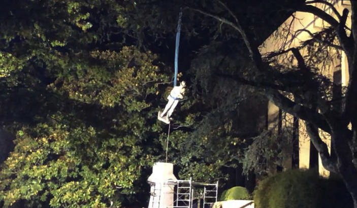 The statue atop the Confederate monument outside the Madison County Courthouse in Huntsville is lifted away from the monument early Friday, Oct. 23, 2020 in Huntsville, Ala. (Paul Gattis/al.com via AP)