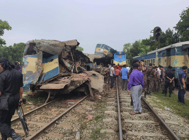 People gather near badly damages coaches after two speeding trains collided in in Brahmanbaria district, 82 kilometers (51 miles) east of the capital, Dhaka, Bangladesh, Tuesday, Nov.12, 2019. More than a dozen people were killed and scores were injured. (AP Photo)