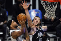Brooklyn Nets guard Bruce Brown, left, shoots as Los Angeles Clippers center Ivica Zubac defends during the first half of an NBA basketball game Sunday, Feb. 21, 2021, in Los Angeles. (AP Photo/Mark J. Terrill)