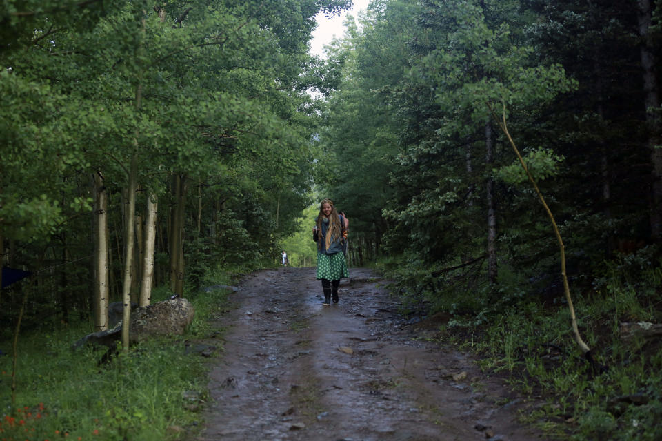 Kendra Strebig walks between encampments at the Rainbow Gathering on Friday, July 2, 2021, in the Carson National Forest, outside of Taos, N.M. More than 2,000 people have made the trek into the mountains of northern New Mexico as part of an annual counterculture gathering of the so-called Rainbow Family. While past congregations on national forest lands elsewhere have drawn as many as 20,000 people, this year's festival appears to be more reserved. Members (AP Photo/Cedar Attanasio)