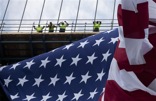 Workers at One World Trade Center watch as an American flag, draped on the building's side, flaps in the wind, Thursday, June 14, 2012 in New York. President Barack Obama is scheduled to visit the site later Thursday. (AP Photo/Mark Lennihan)
