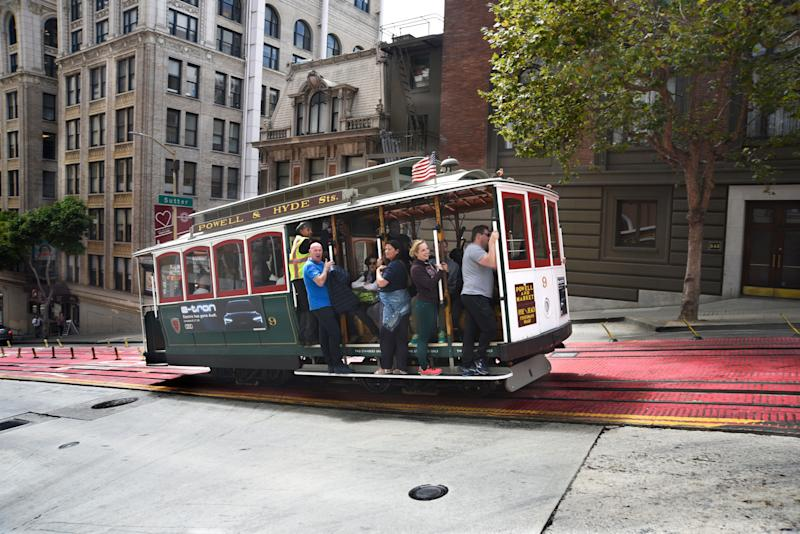 SAN FRANCISCO, CALIFORNIA - SEPTEMBER 14, 2018: Tourists enjoy riding a cable car along Powell Avenue in San Francisco, California. (Photo by Robert Alexander/Getty Images)