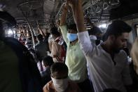 Indian commuters, some wearing protective masks as a precaution against COVID-19 travel in a crowded local train in Mumbai, India, Friday, March 20, 2020. For most people, the new coronavirus causes only mild or moderate symptoms. For some it can cause more severe illness. (AP Photo/Rajanish Kakade)